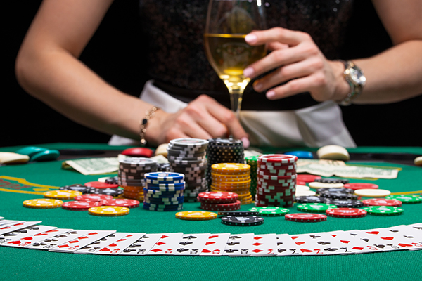 Background of a gaming casino, poker table, cards, chips and a girl with a glass of wine in the background. Background for a gaming business, success